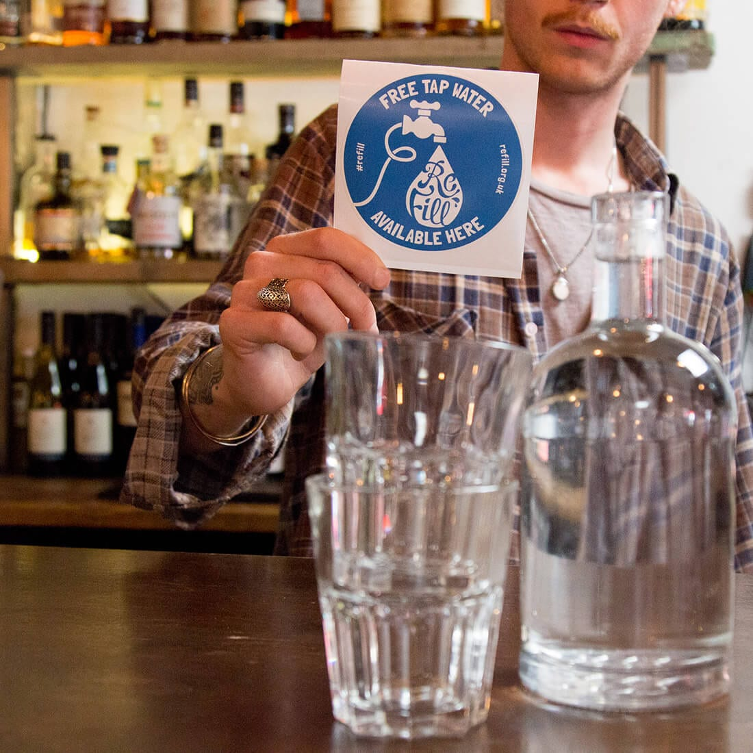 man in bar with Refill sticker and two glasses with a bottle of water