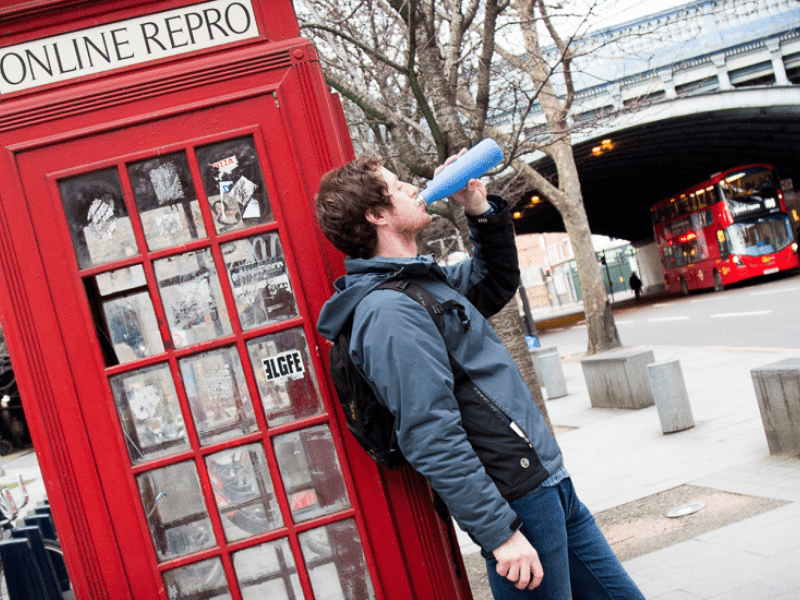 Man drinking from a Refill bottle infront of a red telephone box in London
